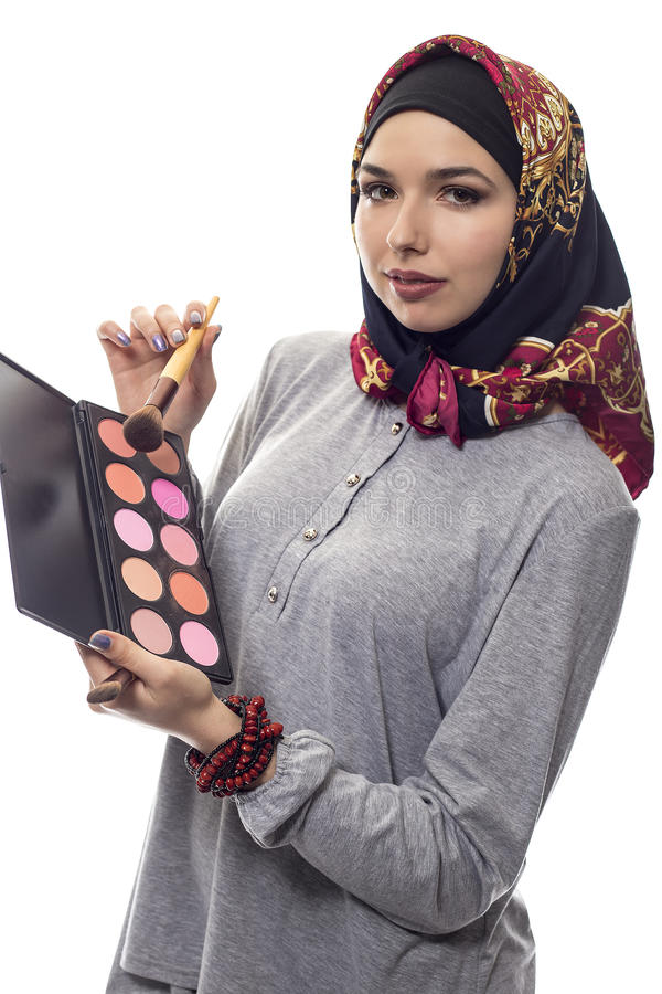 Woman in Hijab as a Make Up Artist. Female make up artist wearing a red hijab with a cosmetic palette to depict conservative fashion. The headscarf is associated stock image