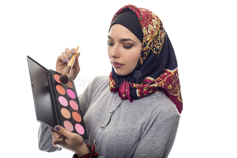 Woman in Hijab as a Make Up Artist. Female make up artist wearing a red hijab with a cosmetic palette to depict conservative fashion. The headscarf is associated royalty free stock photo