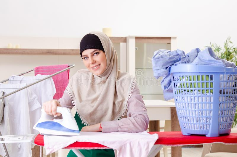 Woman in hijab doing clothing ironing at home stock image