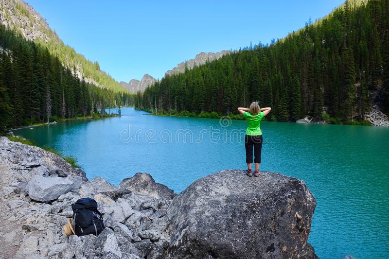 Woman hiker by alpine blue lake. stock photography
