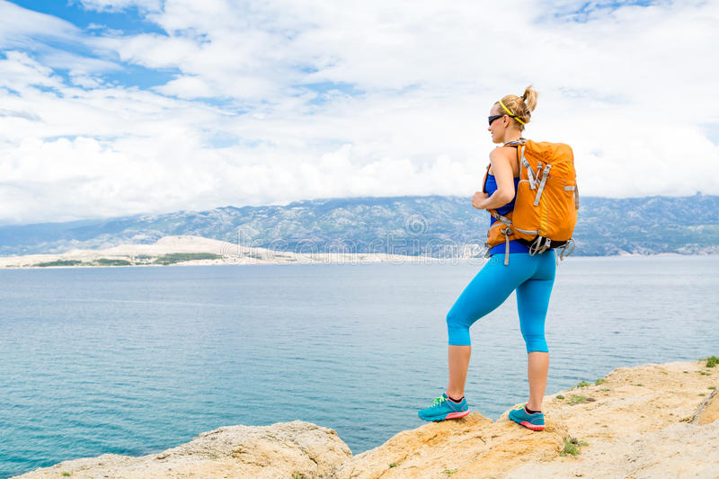 Woman hiker with backpack, hiking at seaside and mountains royalty free stock photo