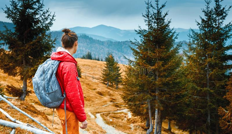Woman hiker with backpack walking outdoors in mountains stock photography