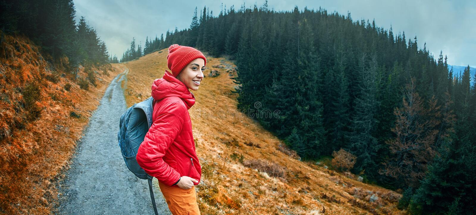 Woman hiker with backpack, wearing in red jacket and orange pants, standing on the mountains background royalty free stock image