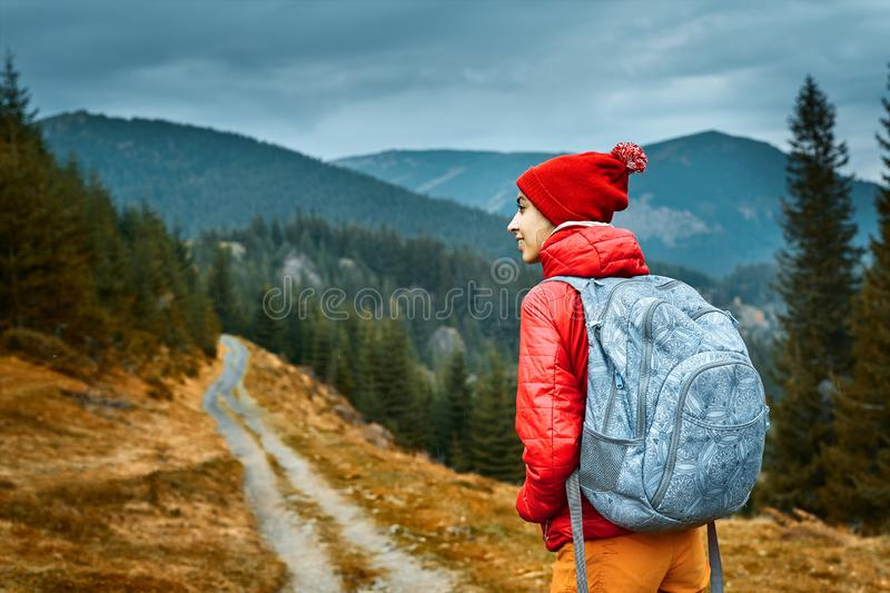 Woman hiker with backpack, wearing in red jacket and orange pants, standing on the mountains background royalty free stock images