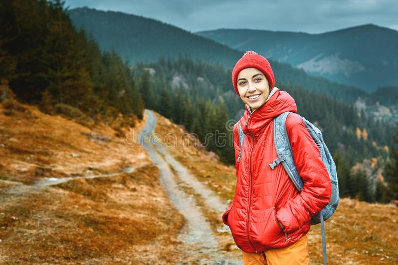 Woman hiker with backpack, wearing in red jacket and orange pants, standing on the mountains background stock photos
