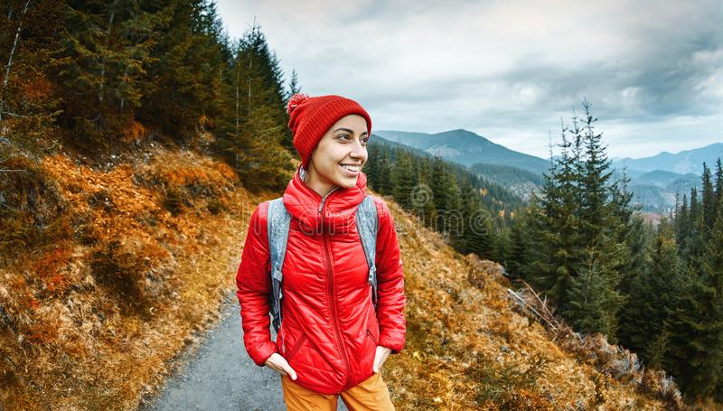 Woman hiker with backpack, wearing in red jacket and orange pants, standing on the mountains background stock image