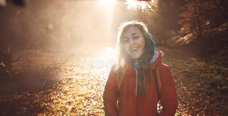 Woman hiker with backpack wearing in red jacket is walking through a foggy autumn woods at the morning and enjoying the stock photos