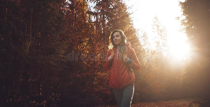Woman hiker with backpack wearing in red jacket is walking through a foggy autumn woods at the morning and enjoying the royalty free stock photos