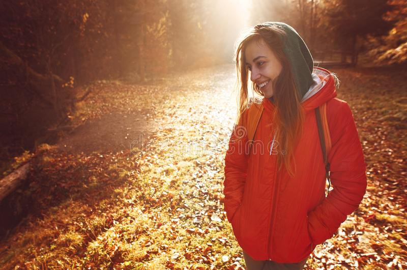 Woman hiker with backpack wearing in red jacket is walking through a foggy autumn woods at the morning and enjoying the stock image