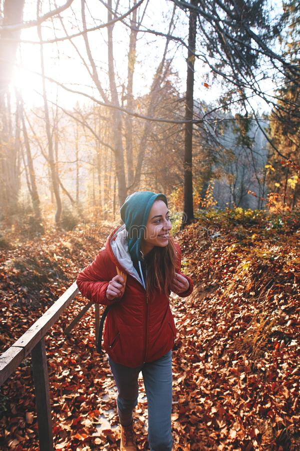 Woman hiker with backpack wearing in red jacket is walking through a foggy autumn woods at the morning and enjoying the stock images