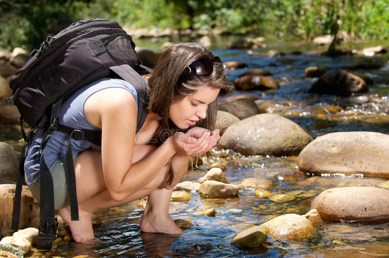 Woman hiker with bag drinking water from stream in nature stock photo
