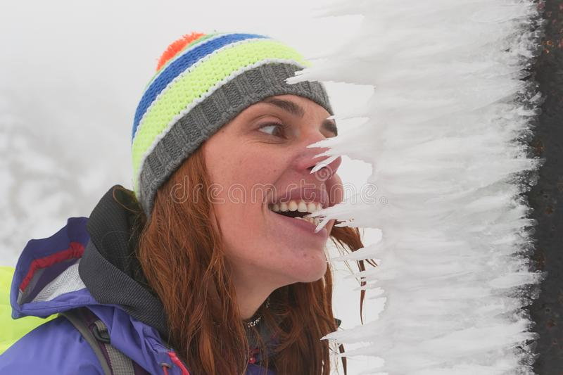 Woman hiker biting on frosted snow, wind blown by heavy winds during a blizzard, in Piatra Craiului mountains, hiking destination. Woman hiker biting on frosted stock image