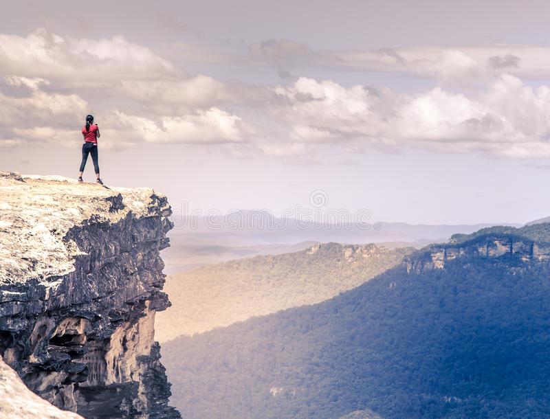 A Woman Hiker Standing On A Cliff Top In Mountains