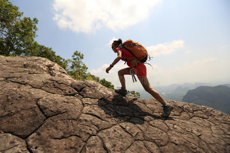 Woman hiker climbing rock on mountain peak cliff. Young asian woman hiker climbing rock on mountain peak cliff royalty free stock photos
