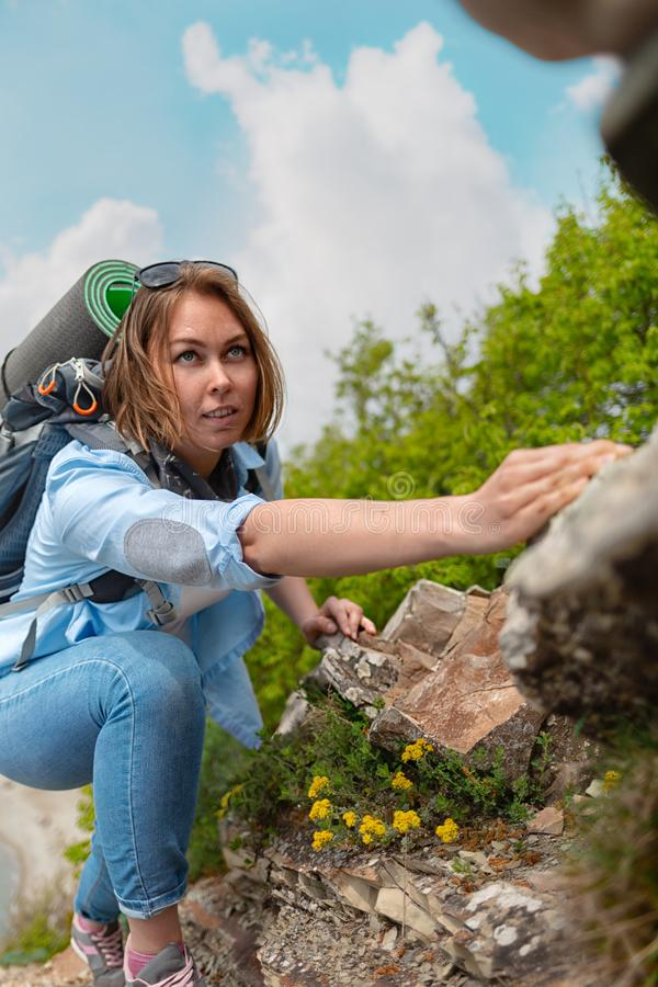 Woman hiker climbing up a rocky mountain path, clutching at the stones. Trees and sky in the background royalty free stock photo