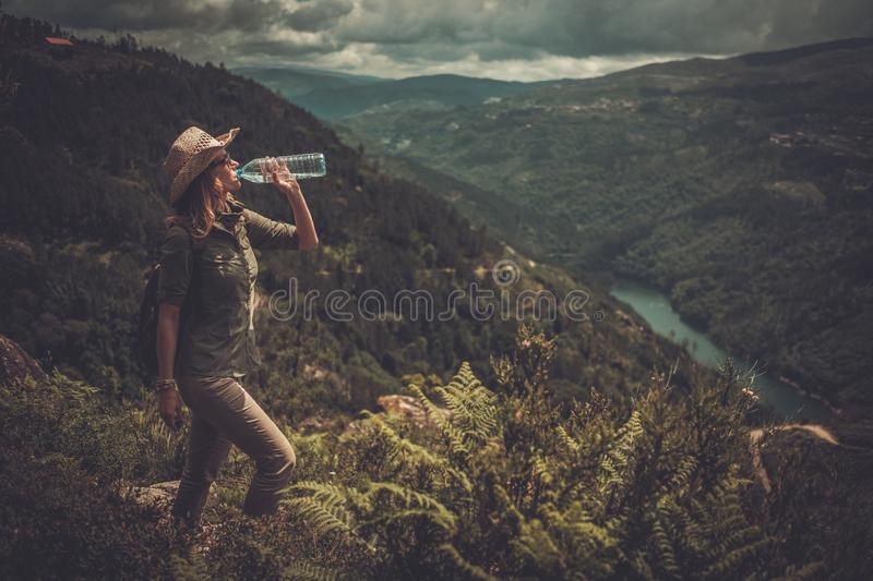 Woman hiker drinking fresh water from a bottle on a top of mountain. royalty free stock image