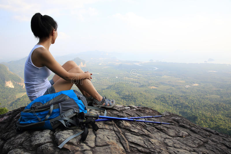 Woman hiker enjoy the view at mountain peak cliff. Woman hiker enjoy the view sitting at sunset mountain peak cliff stock image
