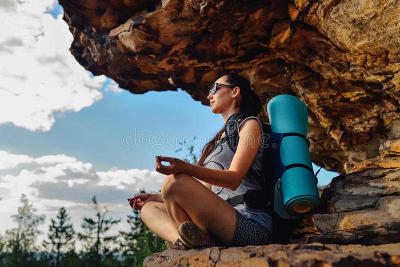 Woman hiker enjoy the view at sunset mountain peak cliff sitting in relax pose.  stock photo