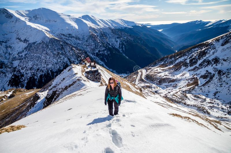 Woman hiker going up on a snowy mountain ridge, in Fagaras mountains, Romania, with the high alpine road Transfagarasan in the bac stock image