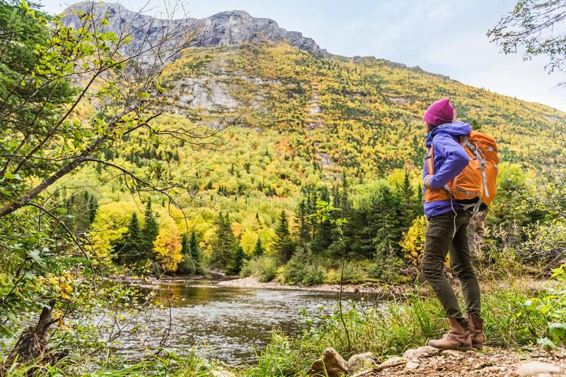Woman hiker hiking looking at scenic view of fall foliage mountain landscape . Adventure travel outdoors person standing relaxing. Near river during nature hike royalty free stock image