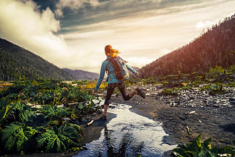 Woman hiker jumps over the small river royalty free stock images