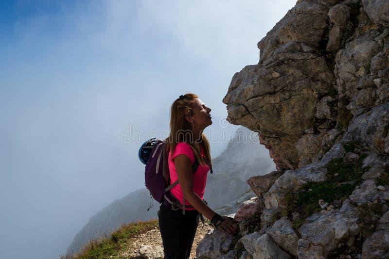 Woman hiker kissing a rock face in the Julian Alps, Slovenia, just under Mangart peak, after descending the via ferrata route. stock photos