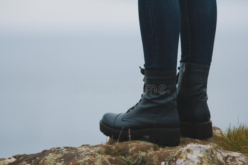 Woman hiker legs in big boots on mountain peak cliff royalty free stock photos