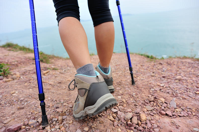 Woman hiker legs walking on seaside mountain trail stock photography