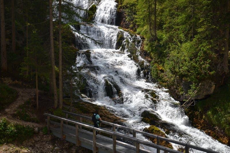 Woman hiker looking at waterfall stock photo