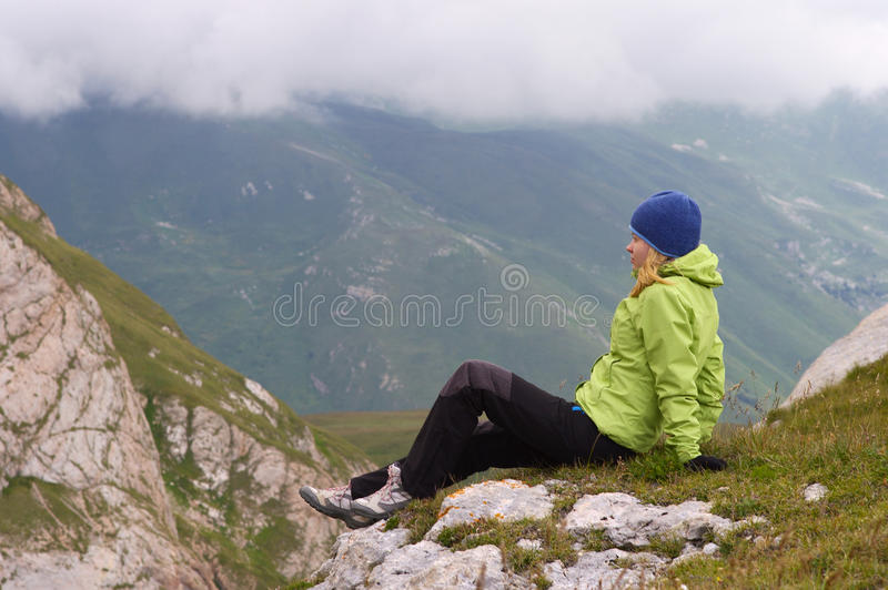 Woman Hiker in Mountains relaxing sitting on rocky cliff. With clouds on background stock photography