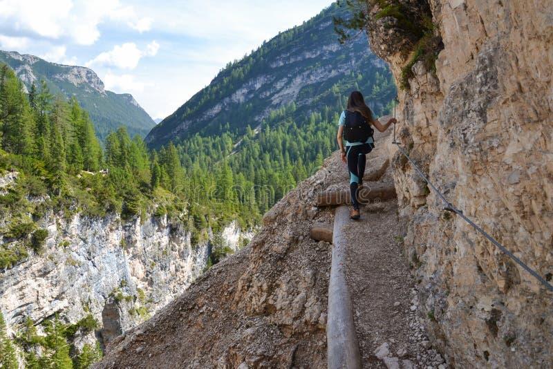 Woman hiker on narrow trail stock photo
