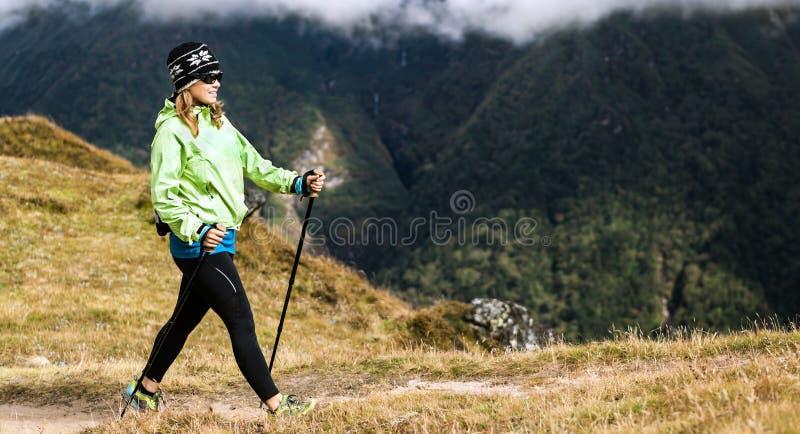 Woman hiker nordic walking in mountains stock photo