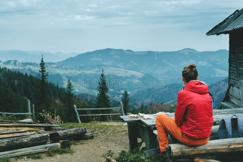 Woman hiker in red jacket and orange pants, sitting on the wooden bench near mountain hut with mountains on background royalty free stock photography