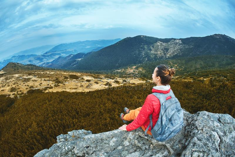 Woman hiker in red jacket sitting on the cliff on high view point in Carpathians mountains royalty free stock image