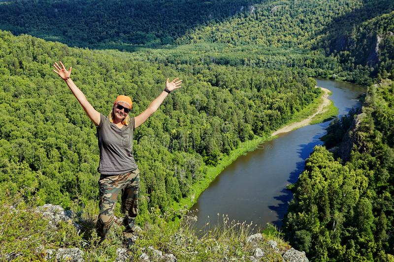 Woman hiker rejoices in conquering the mountain. Pretty smiling woman rejoices in conquering the mountain. She stands at the top, raising her hands up, with a royalty free stock photography