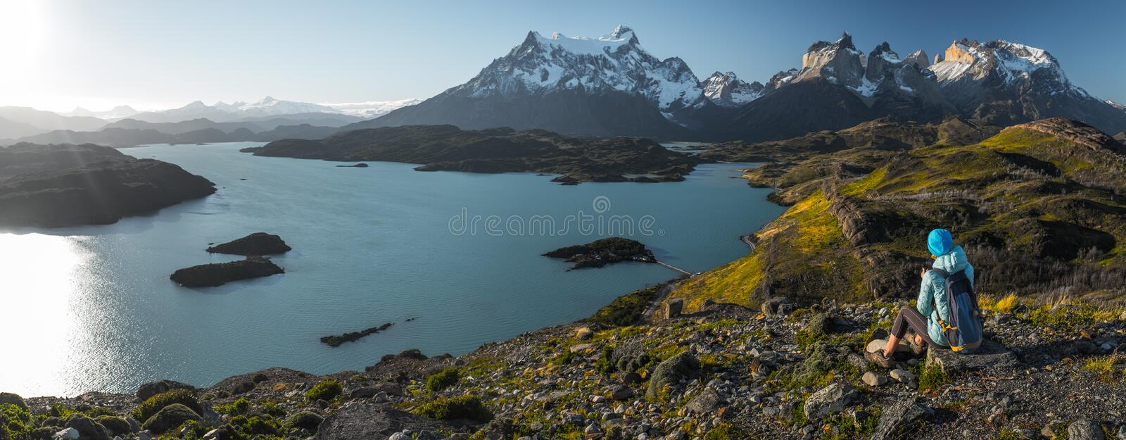 Woman hiker. Sits on the rock and enjoys spectacular view from Mirador Condor of the snow caped mountains and the blue lake in the Torres del Paine National royalty free stock photos