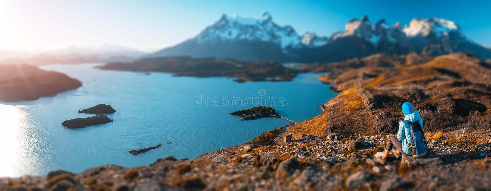 Woman hiker. Sits on the rock and enjoys spectacular view of the snow capped mountains and the blue lake in the Torres del Paine National Park in Chile. Tilt stock photo
