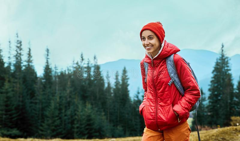 Woman hiker with small backpack wearing in red jacket and orange pants walks by trail through pine woods in the royalty free stock photography
