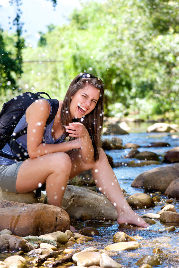 Woman hiker splashing laughing and water from stream stock images
