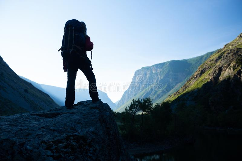 Woman hiker stands with backpack. On the rock and enjoys the mountains view. Altai, Russia stock images