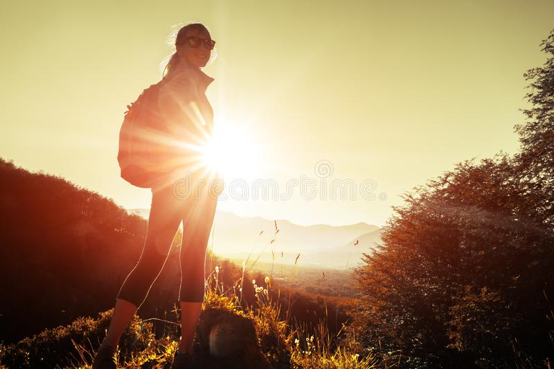 Woman hiker stands in mountains. On the hill, smiles and looks into camera royalty free stock images