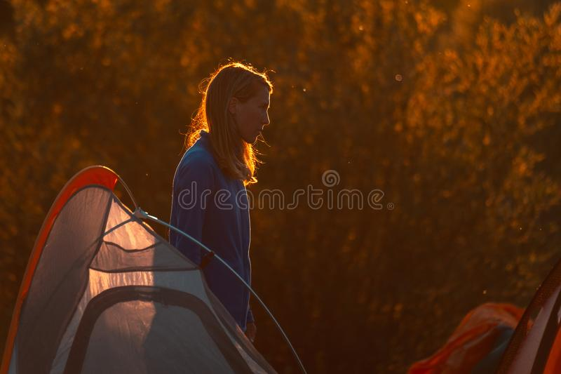 Woman hiker. Stands near the tent highlighted by warm sunset light stock image