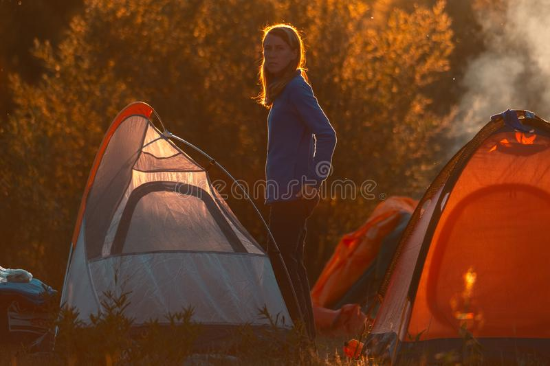 Woman hiker. Stands near the tent highlighted by warm sunset light and looks at the camera stock images