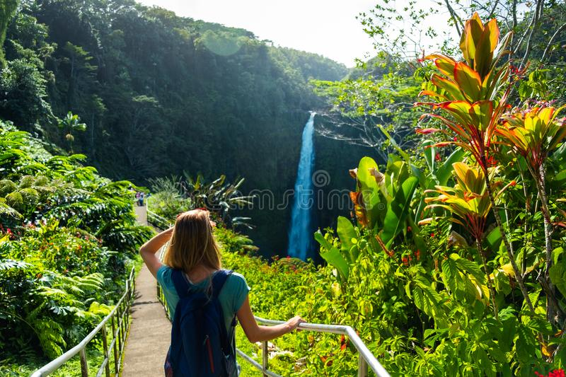 Woman hiker. Stands on the path and watches waterfall in the tropical forest stock photography