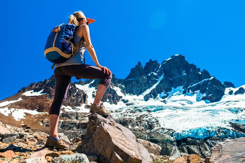 Woman hiker stands on the rocks. And enjoys glacier view of the Cerro Castillo Mountain, Patagonia, Chile stock image
