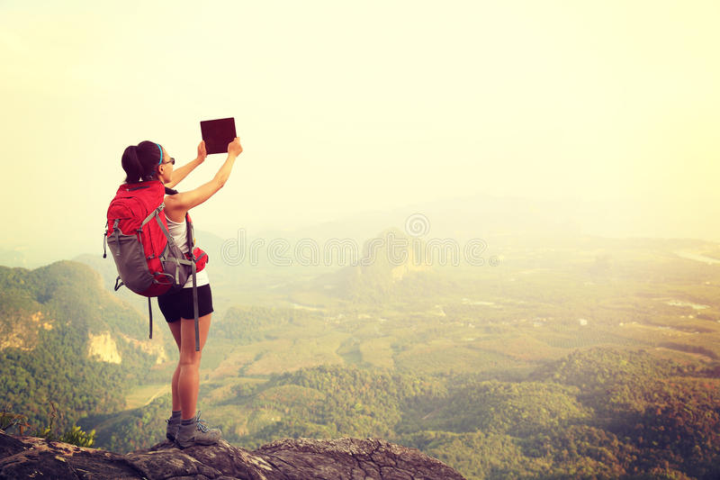 Woman hiker taking photo with digital camera royalty free stock photography