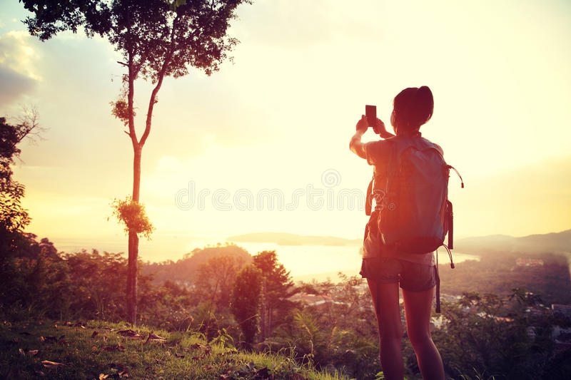 Woman hiker taking photo with digital camera stock photography