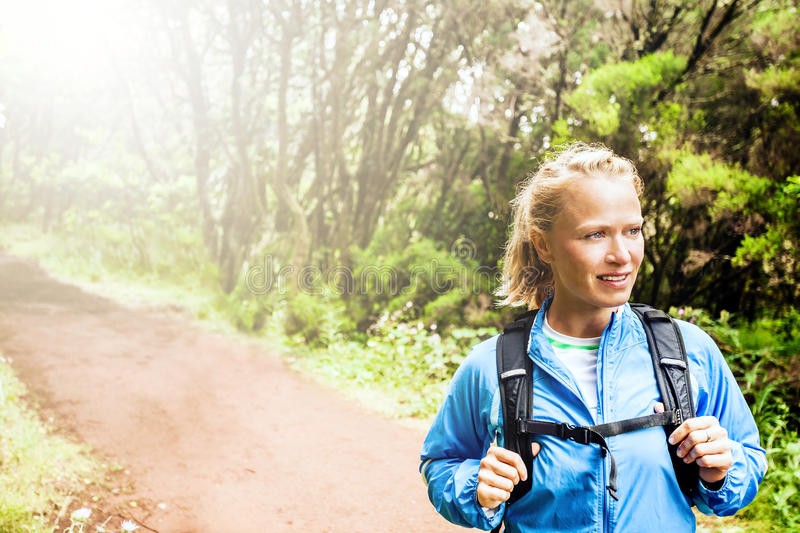 Woman hiker or trail runner in green forest stock photo