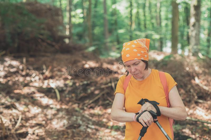 Female hiker using smart wristband during trekking in nature royalty free stock images
