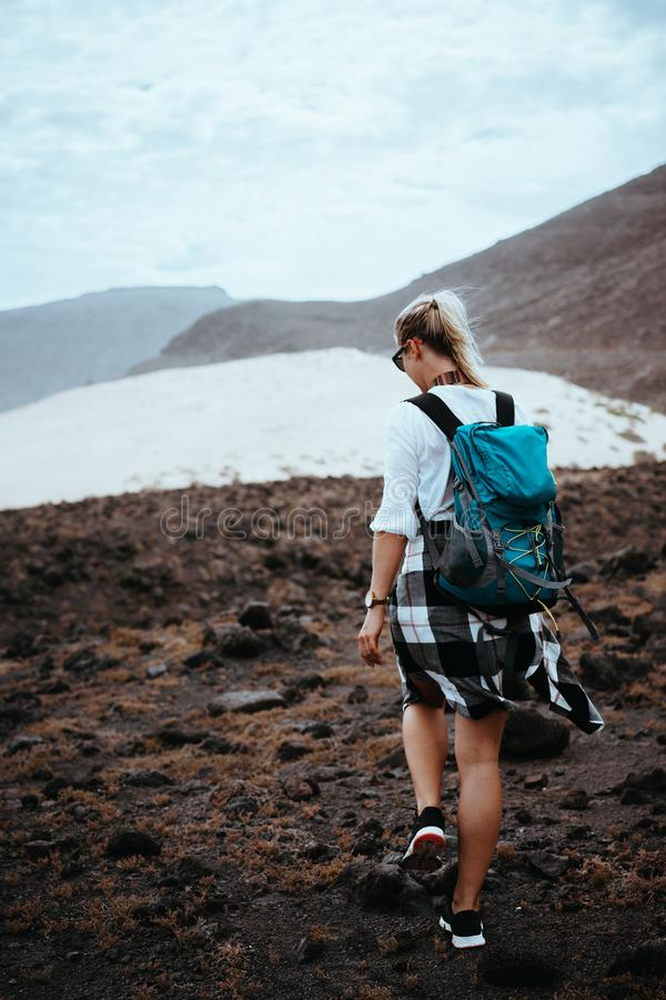 Woman hiker walking on barren rocky terrain among black volcanic boulders and white sand dunes. Sao Vicente Cape Verde royalty free stock photography